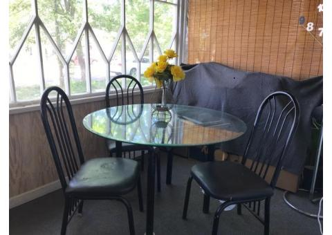 Round glass dining room table and three